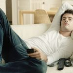 man-relaxing-on-sofa-holding-remote-controls